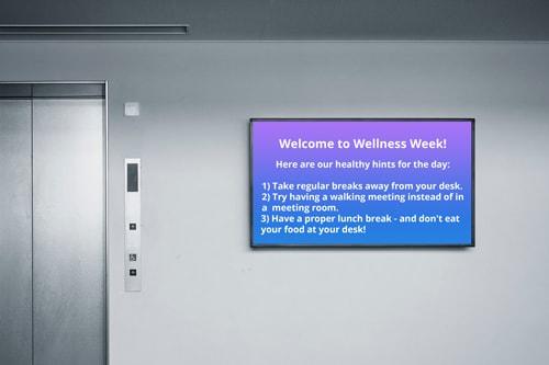 wellness week screensaver on screen by elevator