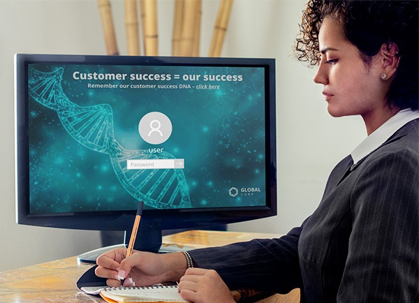 Woman sitting besides customer success lock screen on computer